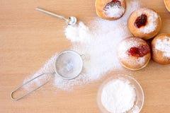 Unordentliche Chanukka-Tabelle mit Zuckerpulver und -donuts lizenzfreie stockbilder