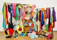 Unordentliche durcheinandergeworfene Frauengarderobe mit bunter Kleidung und Zubehör Lizenzfreie Stockfotos