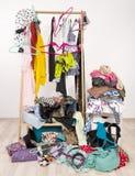Unordentliche durcheinandergeworfene Frauengarderobe mit bunter Kleidung und Zubehör Stockfotos