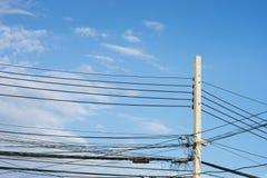 Unordentliche elektrische Drähte und bewölkter Himmel Lizenzfreie Stockfotografie