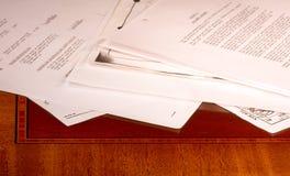Unordentliche Papiere auf Schreibtisch Stockbild