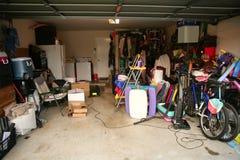 Unordentliche verlassene Garage voll des Materials Stockbilder