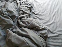 Unordentliche zerknitterte Decke ist auf dem Bett stockfoto