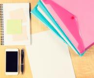 Unordentlicher Bürotisch mit Smartphone, Notizblock und füllenden Ordnern Ansicht von oben Stockbild