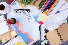 Unordentlicher Schreibtisch mit Geschäftsbericht Lizenzfreie Stockbilder