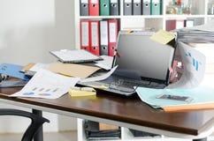 Unordentlicher und durcheinandergeworfener Schreibtisch Stockbild