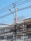 Unordnung des elektrischen Drahtes auf Polen nahe Gebäude lizenzfreies stockfoto