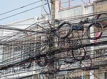 Unordnung des elektrischen Drahtes auf Polen nahe Gebäude stockfotos