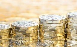 Unosić się sterty złociste monety z monety tłem Zdjęcia Stock