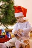 Unpack gift-box. Litle girl unpack gift-box Royalty Free Stock Photo