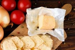 Unpacked aromatic romadur cheese on chopping board Royalty Free Stock Photos
