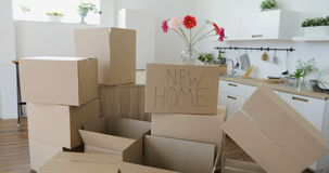 Unpacking boxes in new home and putting things away in kitchen, big cardboard boxes in new home. Moving to a new. New home owners unpacking boxes, footage of big stock footage