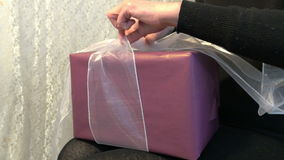 Unpacking a gift 4K. A close up of a woman unpacking a festively wrapped present box with a satin bow stock video footage