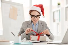 Unpacking gift. Smiling young impatient employee untying red ribbon on top of package with xmas gift Royalty Free Stock Photo