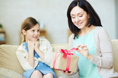 Unpacking gift. Woman unpacking present for mother day from her daughter Royalty Free Stock Images