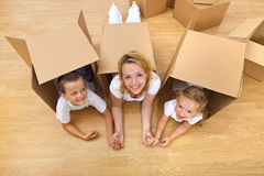 Unpacking in a new home. Family unpacking in a new home having fun on the floor Royalty Free Stock Image