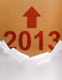 Unpacking the new year 2013. Torn wrapping paper revealing the new and better year Stock Image