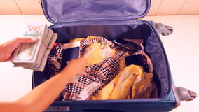 Unpacking the suitcase full of money and summer clothes stock footage