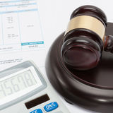 Unpaid bill with calculator and wooden gavel over it series - close up studio shot Royalty Free Stock Photos