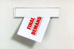 Unpaid bill through the letterbox. Final demand notice on letter being delivered through a letterbox concept for unpaid bill, late payment and repayment Royalty Free Stock Images