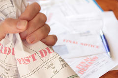 Unpaid Overdue Bills Clutched in Hand Royalty Free Stock Image