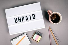 Unpaid. Text in light box royalty free stock image