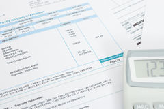 Unpaid utility bill and calculator over it - close up studio shot. Unpaid utility bill and calculator over it series - close up studio shot Royalty Free Stock Images