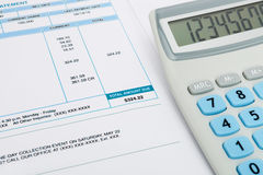 Unpaid utility bill and calculator over it Stock Photos