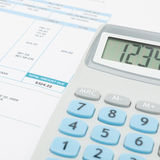 Unpaid utility bill and calculator over it series - close up studio shot Royalty Free Stock Images