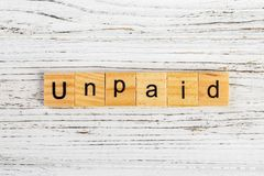 UNPAID word made with wooden blocks concept royalty free stock photography