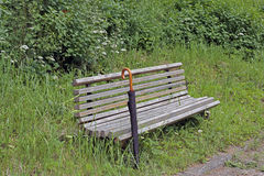 Unpainted ławka i następny czarny parasol Obraz Royalty Free
