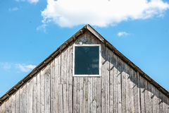 Unpainted old wooden shed with small window Stock Photo