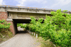 Unpaved country road crossed highway bridge below Royalty Free Stock Image