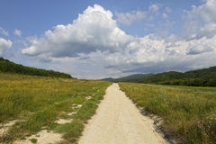 Unpaved dirt road takes to the sky with clouds.  Royalty Free Stock Photo