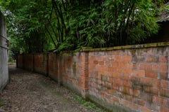 Unpaved footpath along red-brick enclosure Stock Photo