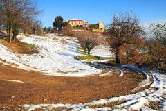 Unpaved road in countryside. Countryside unpaved road among snowy hills of Piedmont, northern Italy Royalty Free Stock Images
