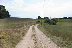 Unpaved road in grassy field against cloudy sky Stock Photo