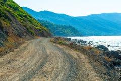 Unpaved road runs along sea Royalty Free Stock Images