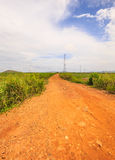 Unpaved road into the rural area. This red soil unpaved road leads us into the middle of nowhere Stock Images