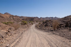 Unpaved road towards hills Stock Photos