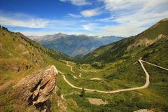Unpaved road in the valley in Alps, italy. Royalty Free Stock Images