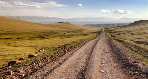 Unpaved road and yurts near Son-Kul lake in Kyrgyzstan. Unpaved road and yurts near Son-Kul lake and Tien shan mountains in Kyrgyzstan royalty free stock photo