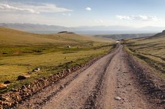 Unpaved road and yurts near Son-Kul lake in Kyrgyzstan. Unpaved road and yurts near Son-Kul lake and Tien shan mountains in Kyrgyzstan royalty free stock images