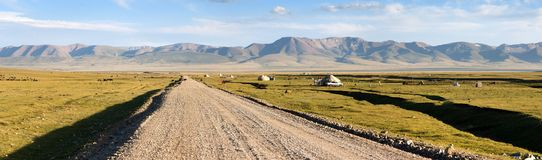 Unpaved road and yurts near Son-Kul lake in Kyrgyzstan. Unpaved road and yurts near Son-Kul lake and Tien shan mountains in Kyrgyzstan royalty free stock photos