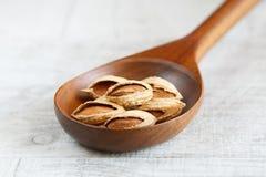 Unpeeled миндалины в деревянной ложке на светлой предпосылке Стоковая Фотография RF