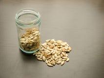 Unpeeled семена тыквы внутри стеклянного опарника, с некоторыми лить семенами стоковые фото