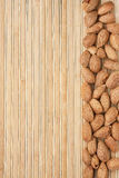 Unpeeled almonds lying on a bamboo mat Stock Image