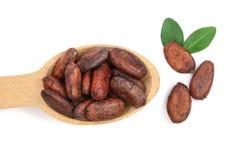 Unpeeled cacaobonen in een houten die lepel met blad op witte achtergrondclose-up hoogste mening wordt geïsoleerd Royalty-vrije Stock Foto's