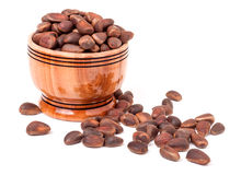 Unpeeled cedar nuts in a wooden barrel on white background Royalty Free Stock Images
