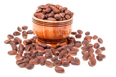 Unpeeled cedar nuts in a wooden barrel on white background Royalty Free Stock Image